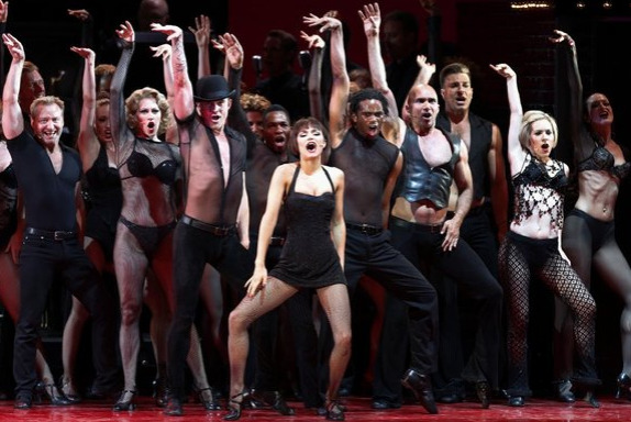 """'Chicago' Samantha Barks, center, as Velma Kelly in the Los Angeles Philharmonic's performance of the musical """"Chicago,"""" directed by Brooke Shields, with musical director and conductor Rob Fisher at the Hollywood Bowl."""