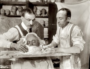2 men in the process of making a death mask