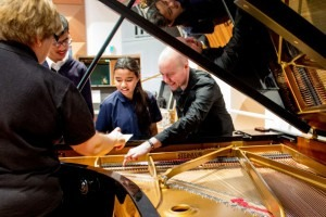 Victorian College for the Deaf student Yvonne (centre) explores a grand piano with Melbourne Symphony Orchestra pianist Leigh Harold (right).774 ABC Melbourne: Simon Leo Brown