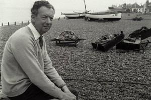 Benjamin Britten on the shingle at Aldeburgh, fishing boats behind him.