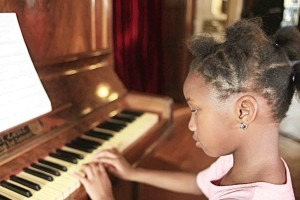 A young girl playing music on a piano