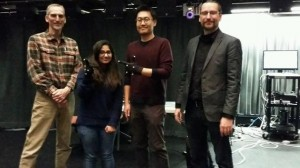 """Teaching a Computer to Transform Data Into Sound. Woohun Joo(second from right) wears motion capture gloves to 'conduct' music and sound in the """"Cube"""" at Virginia Tech. L to R, Greg Earl, Disha Sardana, Woohun Joo, Ico Bukvic"""