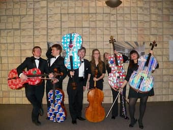 Cellists enfolded their instruments in gift wrap for their Christmas concerts